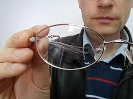 man holding scratched glasses